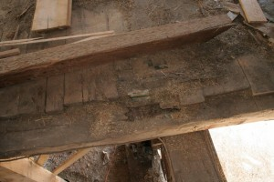 Removing materials like flooring often reveals hidden deterioration like the large void in this bent joist caused by a roof leak far above.