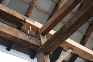 Replacement timbers are joined to originals using the traditional joinery.  Steel straps at unions show where existing joinery has been supplemented to resist tension loads.