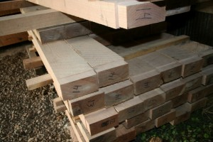 Stacks of floor joists with square-ruled ends waiting to drop into their bearing pockets.