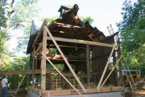New replacement timber framing is guyed back by temporary bracing.
